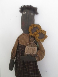 "Sadie is 30"" tall. She holds 2 sunflowers on sticks and a bag with ""SEEDS"" hand-stitched on a piece of muslin on the front."