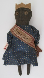 "13"" Libby wears a banner with the word ""Freedom"" hand-stitched on it.  The banner is held together with a rusty bell.  $33.00"