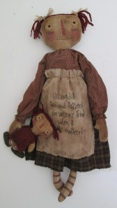 "26"" Anna never goes anywhere without her rag doll, Belle.  She loves her so much that she even stitched a poem about her on her apron.  Made to hang but can also sit.  $58.00"