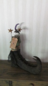 "Pair of witch boots are  21""Hx16""W.  They are tied together with black cheesecloth and have a grubby hand-lettered tag ""Hocus Pocus"".  There are 2 stars, a moon and a bat sticking out of the top of the boots and each boot has four rusty bells sewn down the front.  $62.00"