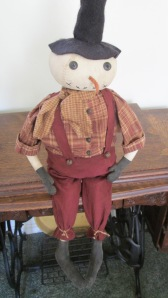 "Sheldon is 28"" tall to the top of his hat and weighted to sit.  He is made of painted muslin and has gruuby flannel clothes and a wool felted hat.  Rusty bells are sewn down the front of his shirt and his suspenders are attached with rusty bells.  $52.00"