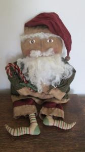 "Santa is 22"" tall and made of grungy muslin. His sheep's wool beard and hair are sewn on - Never glued. His clothes are grubby flannel with grubby flannel trim hand-sewn on. $68.00"